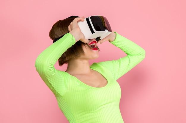 Młoda kobieta w zielonej koszuli i szarej spódnicy wypróbowuje grę w wirtualnej rzeczywistości