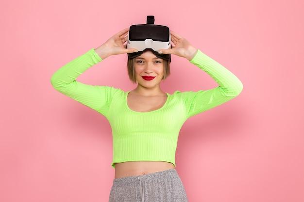 Młoda kobieta w zielonej koszuli i szarej spódnicy z uśmiechem wypróbowuje wirtualną rzeczywistość