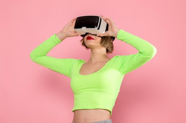 Młoda kobieta w zielonej koszuli i szarych spodniach wypróbowuje grę w wirtualnej rzeczywistości