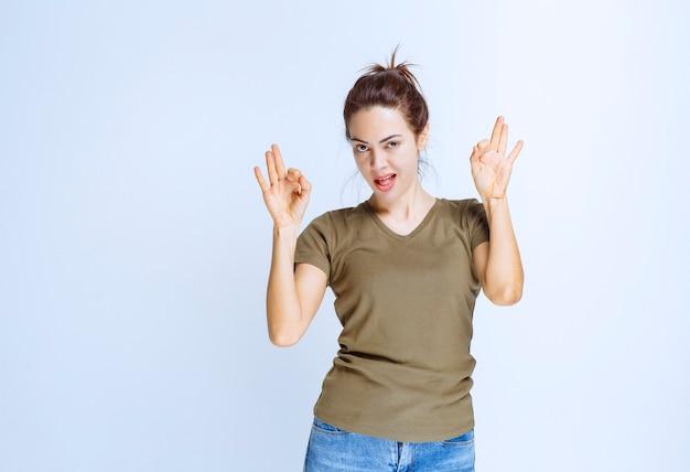 Młoda kobieta w zielonej koszuli pokazujący znak przyjemności