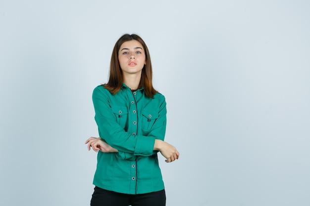 Młoda kobieta w zielonej koszuli pozuje ze skrzyżowanymi rękami przed sobą i wygląda pewnie, widok z przodu.