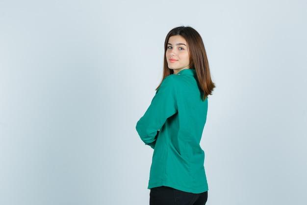 Młoda kobieta w zielonej koszuli, trzymając ręce złożone, patrząc wstecz i patrząc wesoło, widok z tyłu.