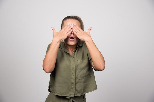 Młoda kobieta w zielonej koszuli zasłaniając jej oczy.