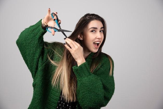 Młoda kobieta w zielonej kurtce cięcia jej włosy nożyczkami.