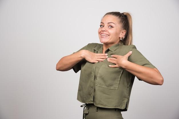Młoda kobieta w zielonej kurtce czuje się szczęśliwa.