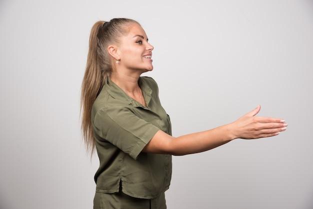 Młoda kobieta w zielonej kurtce oferuje jej rękę trząść.