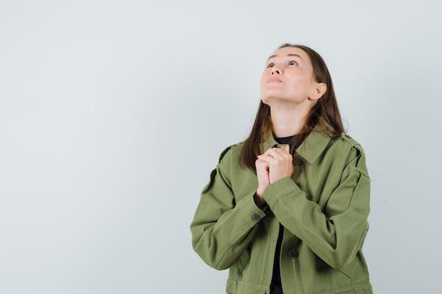 Młoda kobieta w zielonej kurtce pokazując gest modlitwy i patrząc bezradny, przedni widok.