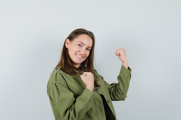 Młoda kobieta w zielonej kurtce pokazując gest zwycięzcy i patrząc wesoło, widok z przodu.