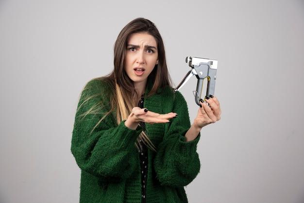 Młoda kobieta w zielonej kurtce pokazuje narzędzie pracy.
