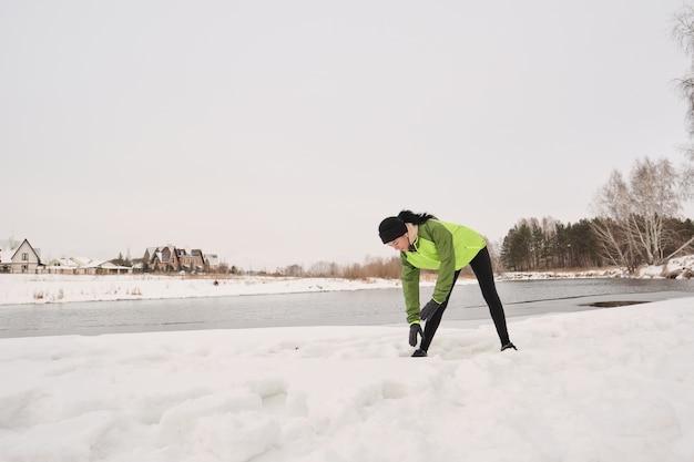 Młoda kobieta w zielonej kurtce stojącej t zimowe jezioro i pochylając się podczas wykonywania rozgrzewki