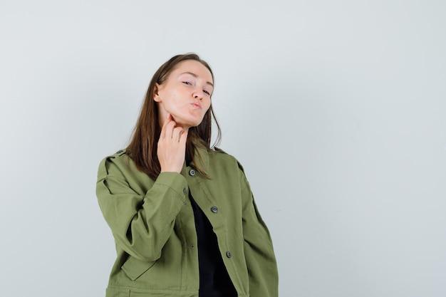 Młoda kobieta w zielonej kurtce wysyłając pocałunek, widok z przodu.