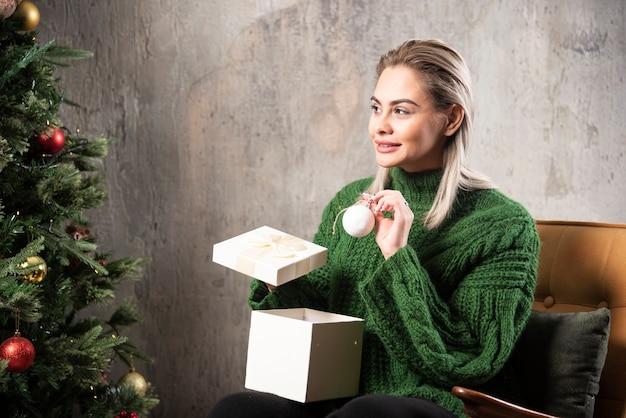 Młoda kobieta w zielonym ciepłym swetrze siedzi i pozuje z pudełkiem