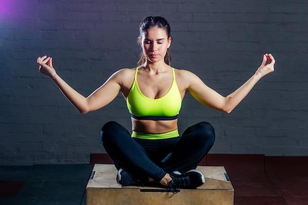 Młoda kobieta w zielonym sportowym staniku i czarnych spodniach siedzi na pudełku w pozycji jogi z czarnymi klockami...