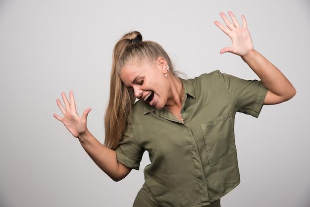 Młoda kobieta w zielonym stroju czuje się szczęśliwa.