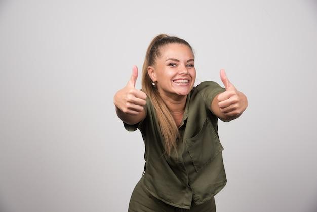 Młoda kobieta w zielonym swetrze daje aprobatom na szarej ścianie.