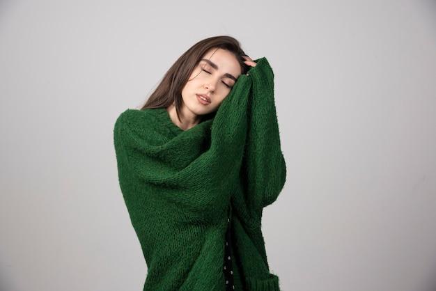 Młoda kobieta w zielonym swetrze śpi na szaro.