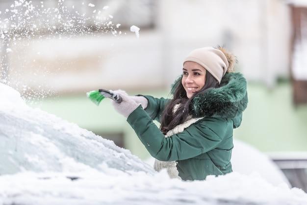 Młoda kobieta w zimowe ubrania czyści samochód ze śniegu poza blokiem w zimie.