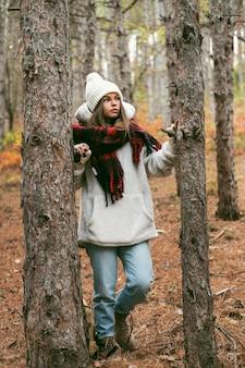 Młoda kobieta w zimowe ubrania stojący obok drzew