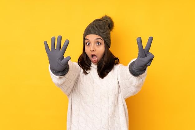 Młoda kobieta w zimowym kapeluszu na odosobnionym żółtym tle, licząc siedem palcami