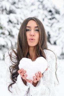 Młoda kobieta w zimowym lesie trzyma serce ze śniegu i wysyła jej pocałunek.