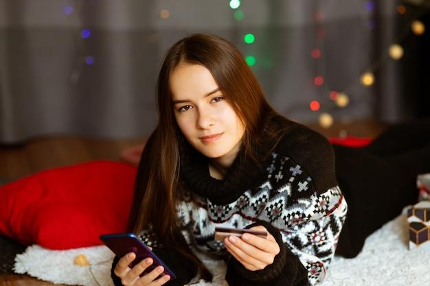 Młoda kobieta w zimowym swetrze robi świąteczne zakupy przez telefon w domu online