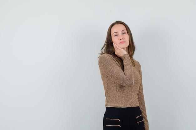 Młoda kobieta w złocistym swetrze i czarnych spodniach, opierając policzek na dłoni i wyglądająca atrakcyjnie