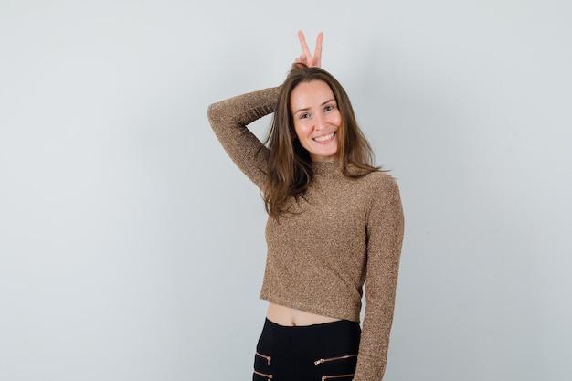Młoda kobieta w złoconym swetrze i czarnych spodniach podnosi palce nad głową jak uszy królika i wygląda na szczęśliwą