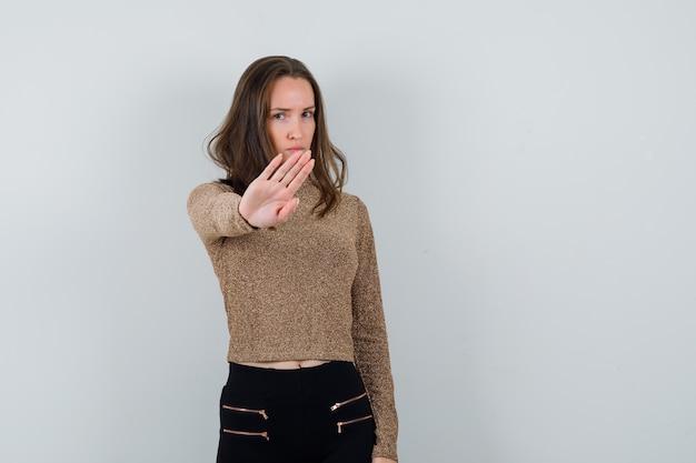Młoda kobieta w złoconym swetrze i czarnych spodniach pokazuje gest stopu i wygląda poważnie