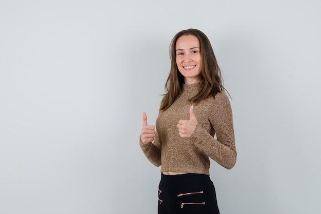 Młoda kobieta w złoconym swetrze i czarnych spodniach pokazuje kciuki do góry i wygląda na szczęśliwą