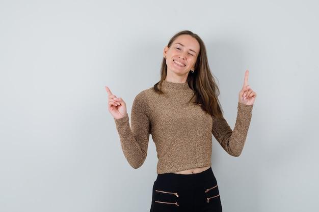 Młoda kobieta w złoconym swetrze i czarnych spodniach skierowana w górę palcami wskazującymi, mrugająca i wyglądająca na szczęśliwą