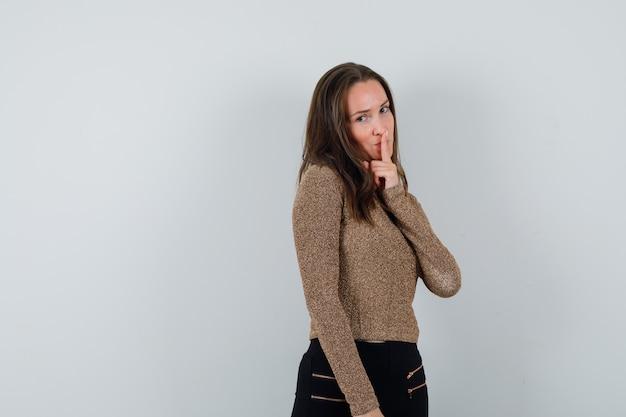 Młoda kobieta w złoconym swetrze i czarnych spodniach trzyma palec wskazujący na ustach, pokazując gest ciszy i patrząc poważnie