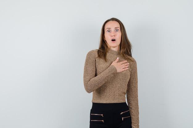 Młoda kobieta w złoconym swetrze i czarnych spodniach trzyma rękę na piersi i wygląda na zaskoczonego