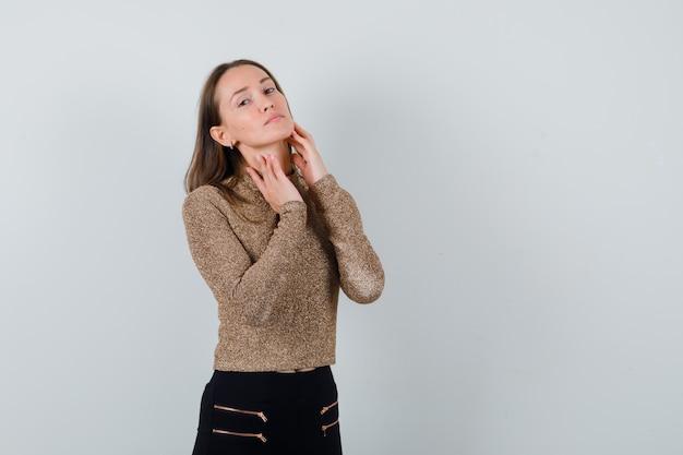 Młoda kobieta w złoconym swetrze i czarnych spodniach trzyma rękę na szyi i wygląda uroczo