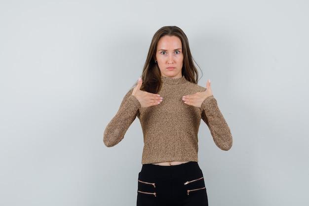 Młoda kobieta w złoconym swetrze i czarnych spodniach, wskazując na siebie i patrząc poważnie
