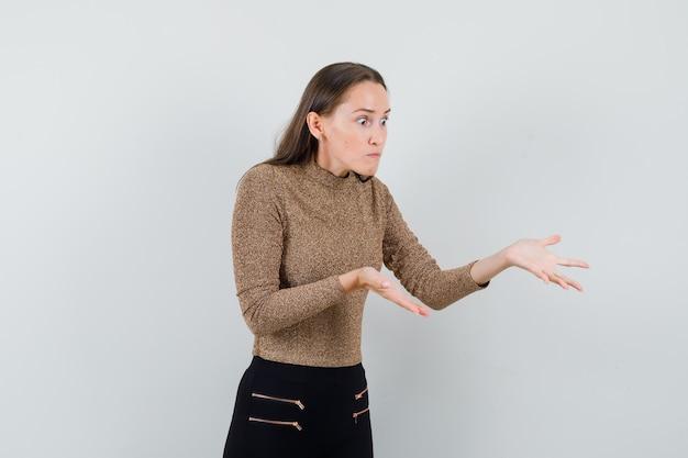 Młoda kobieta w złoconym swetrze i czarnych spodniach wyciąga ręce, by coś odebrać i wygląda na zszokowaną, widok z przodu.