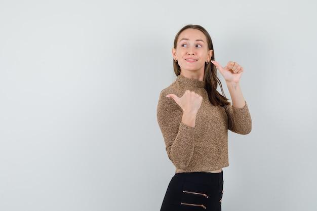 Młoda kobieta w złotej bluzce patrząc wstecz, pokazując kciuk w górę i patrząc zadowolony. miejsce na tekst
