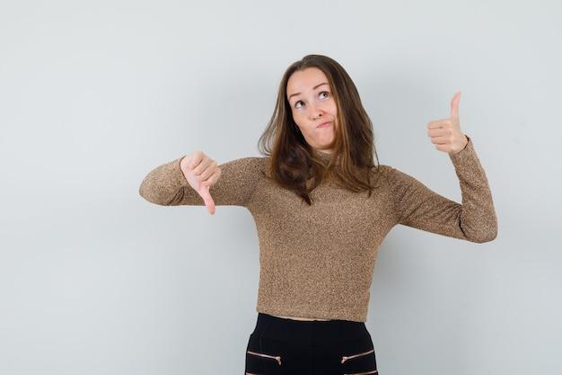 Młoda kobieta w złotej bluzce pokazuje kciuk w górę iw dół i wygląda zdziwiony