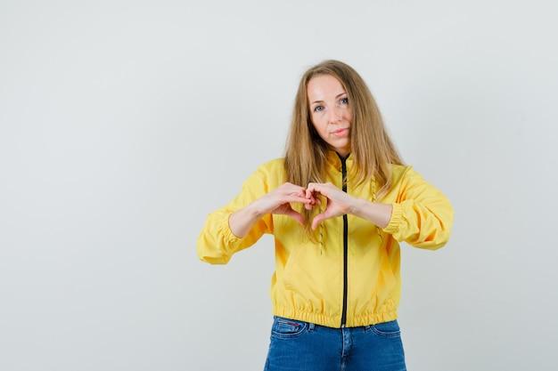 Młoda kobieta w żółtej bomber kurtce i niebieskiej dżinsach pokazuje gest serca i wygląda uroczo, widok z przodu.