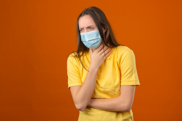 Młoda kobieta w żółtej koszulce polo i medycznej masce ochronnej czuje się źle i bóle gardła stojąc na pomarańczowym tle