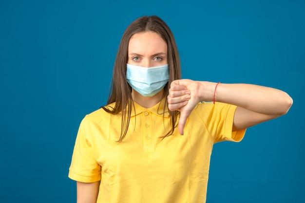 Młoda kobieta w żółtej koszulce polo i medycznej masce ochronnej czyniąc kciuk w dół znak poważnie patrząc na kamery na na białym tle niebieskim tle