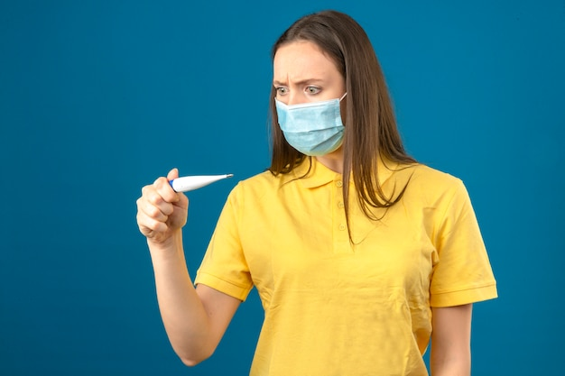 Młoda kobieta w żółtej koszulce polo i medycznej masce ochronnej patrząc na termometr w panice na na białym tle niebieskim tle