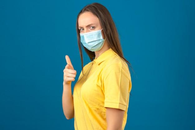 Młoda kobieta w żółtej koszulce polo i medycznej masce ochronnej, wskazując palcem na aparat z poważną twarzą stojącą na niebieskim tle na białym tle