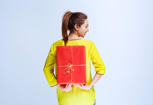 Młoda kobieta w żółtej koszuli chowa za sobą czerwone pudełko upominkowe