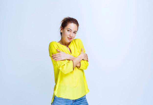 Młoda kobieta w żółtej koszuli krzyżuje ramiona i czuje zimno