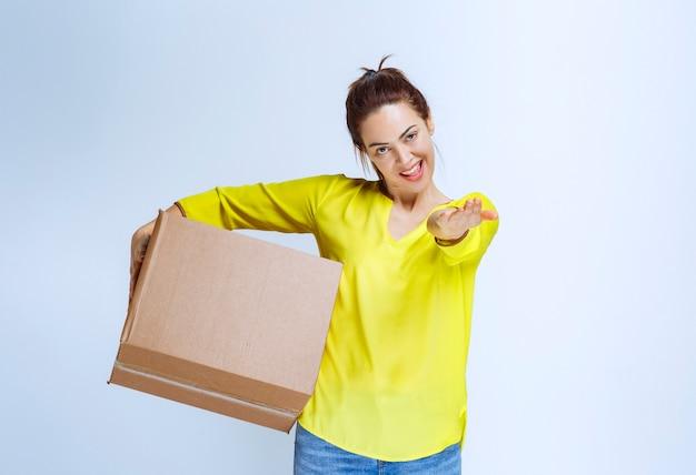 Młoda kobieta w żółtej koszuli oferująca kartonowe pudełko
