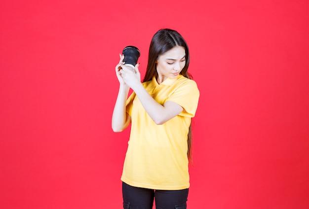 Młoda kobieta w żółtej koszuli trzyma czarną jednorazową filiżankę kawy i odmawia jej przyjęcia