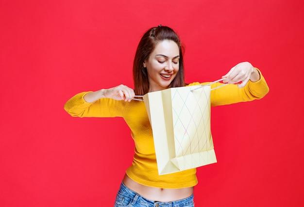 Młoda kobieta w żółtej koszuli trzyma kartonową torbę na zakupy i sprawdza, co jest w środku