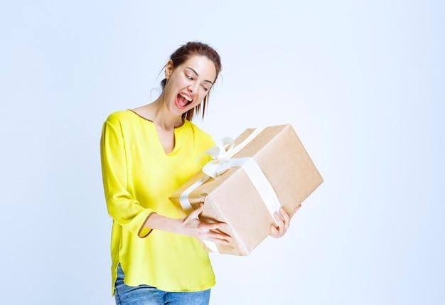 Młoda kobieta w żółtej koszuli trzyma kartonowe pudełko i krzyczy ze szczęścia