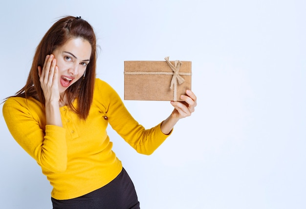 Młoda kobieta w żółtej koszuli trzyma kartonowe pudełko i wygląda na zaskoczoną