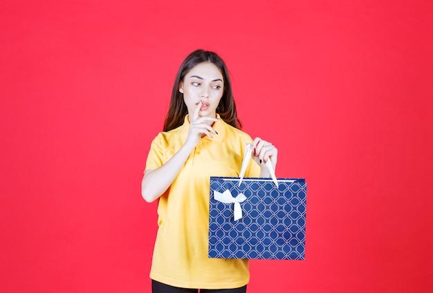 Młoda kobieta w żółtej koszuli trzyma niebieską torbę na zakupy i wygląda na zdezorientowaną i zamyśloną